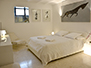 4th bedroom with large double bed and TV, everything in white
